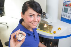 Photograph of a female dental technician holding a dental bridge and smiling.