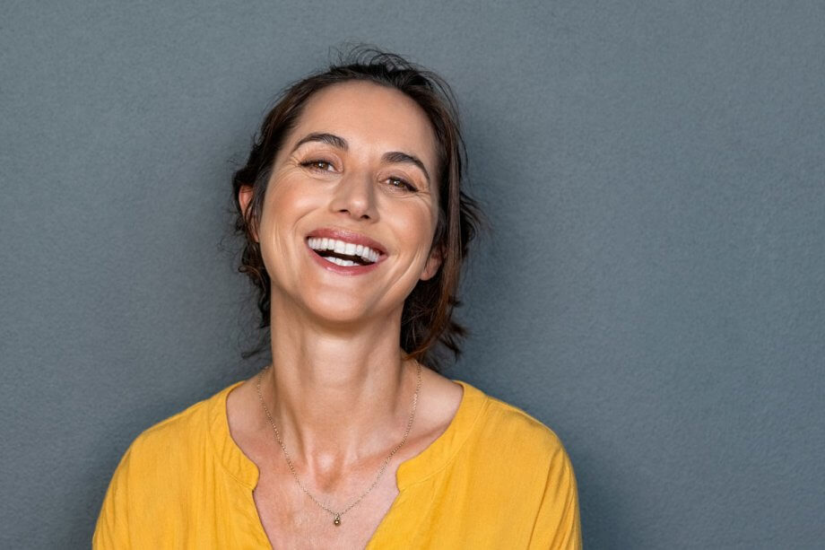 smiling woman in yellow shirt standing against grey background