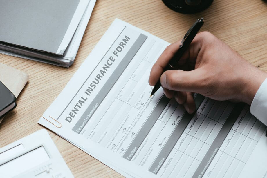 man's hand filling out dental insurance form