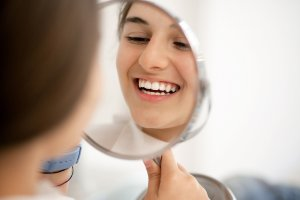 young woman looking in mirror and smiling