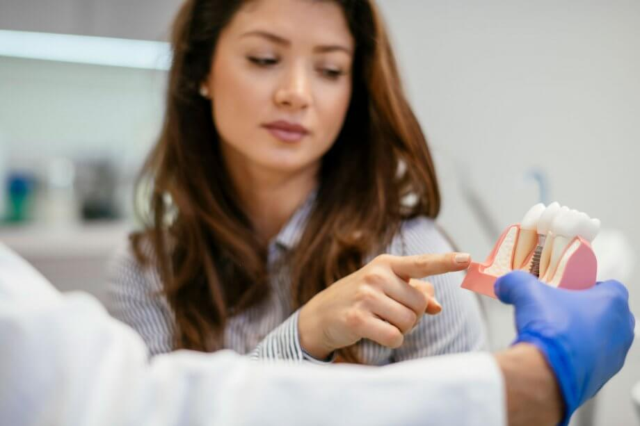 woman in dental chair pointing at dental implant model